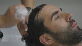 Le mani del parrucchiere versano l'acqua ai capelli del ` s del cliente Il cliente lava i capelli dopo il taglio nel parrucchiere archivi video