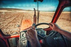 Le mani del primo piano dell'agricoltore, si siede dentro nella cabina del trattore Immagini Stock