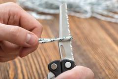 Le mani del primo piano dell'uomo taglia la corda facendo uso di multi strumento con la lama seghettata Fotografia Stock Libera da Diritti