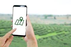Le mani del primo piano facendo uso dello smartphone aprono l'applicazione di GIS e di GPS con immagine stock libera da diritti