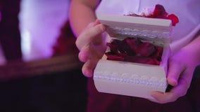 Le mani del primo piano del ragazzo aprono la bella scatola di legno bianca in cui anello di oro di menzogne sui petali delle ros video d archivio
