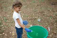 Le mani del ` s del bambino su variopinto riciclano nei guanti blu del lattice Fuori della foto, della terra e dei rifiuti sui pr Immagini Stock Libere da Diritti