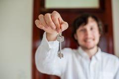 Le mani del ` s degli uomini tengono la chiave della casa su un fondo di una porta di legno Possesso del concetto del bene immobi fotografie stock