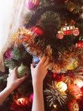 Le mani del ` s dei bambini decorano l'albero di Natale Immagine Stock Libera da Diritti
