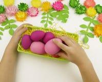 Le mani del ` s dei bambini hanno messo le uova di Pasqua in un canestro verde pasqua Preparazione per il partito di Pasqua Fotografie Stock Libere da Diritti