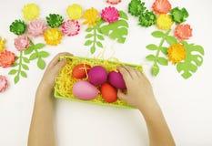 Le mani del ` s dei bambini hanno messo le uova di Pasqua in un canestro verde pasqua Preparazione per il partito di Pasqua fotografia stock libera da diritti