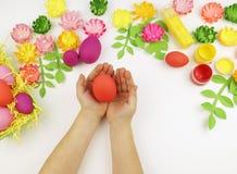 Le mani del ` s dei bambini tengono un uovo di Pasqua pasqua Sorgente Creatività del ` s dei bambini immagini stock