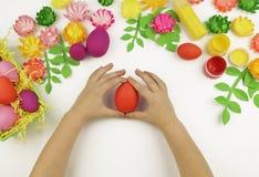Le mani del ` s dei bambini tengono un uovo di Pasqua pasqua Sorgente Creatività del ` s dei bambini immagine stock libera da diritti