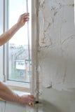 Le mani del ` s del lavoratore stanno installando un angolo di alluminio perforato Fotografie Stock Libere da Diritti