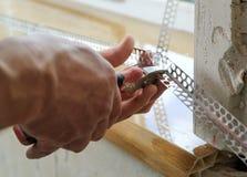 Le mani del ` s del lavoratore stanno tagliando un angolo di alluminio perforato Immagini Stock Libere da Diritti