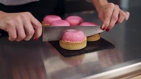 Le mani del ` s della donna hanno tagliato il dessert francese con la glassa rosa dello specchio su superficie di lavoro sulla cu video d archivio