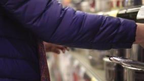 Le mani del ` s della donna si chiudono su Negozio degli articoli nel centro commerciale Giovane donna che sceglie una pentola ne archivi video