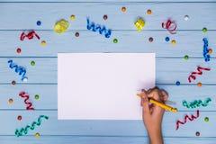 Le mani del ` s della donna tengono la penna e la scrittura sulla carta in bianco bianca con i nastri variopinti intorno Fotografia Stock
