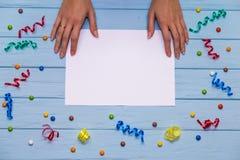 Le mani del ` s della donna tengono la penna e la scrittura sulla carta in bianco bianca con i nastri variopinti intorno Fotografie Stock Libere da Diritti