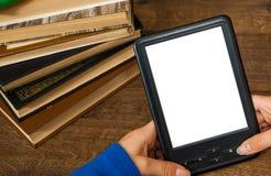 Le mani del ` s della ragazza tengono il libro elettronico sul dispositivo mobile sopra il mucchio di vecchio tascabile con lo sc Fotografia Stock