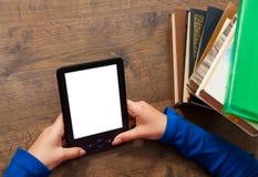 Le mani del ` s della ragazza tengono il libro elettronico sul dispositivo mobile sopra il mucchio di vecchio tascabile con lo sc Immagine Stock Libera da Diritti