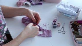 Le mani del ` s delle donne creano un prodotto tessile, il giocattolo, modello stock footage
