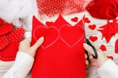 Le mani del ` s delle donne fanno i cuori rossi dal tessuto Preparazione per il giorno del ` s del biglietto di S. Valentino dell Fotografia Stock Libera da Diritti