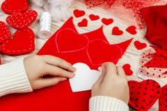 Le mani del ` s delle donne fanno i cuori rossi dal tessuto Preparazione per il giorno del ` s del biglietto di S. Valentino dell Immagini Stock