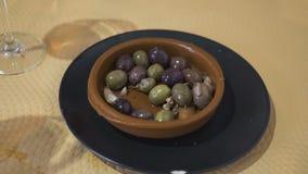 Le mani del ` s delle donne hanno messo le olive da un barattolo di latta in un piatto della porcellana al ristorante archivi video