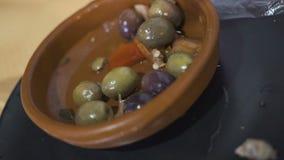 Le mani del ` s delle donne hanno messo le olive da un barattolo di latta in un piatto della porcellana al ristorante video d archivio