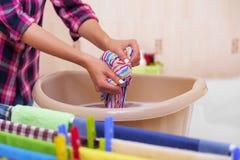 Le mani del ` s delle donne lavano i vestiti nel bacino fotografia stock libera da diritti