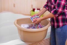 Le mani del ` s delle donne lavano i vestiti nel bacino fotografie stock libere da diritti