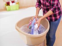 Le mani del ` s delle donne lavano i vestiti nel bacino immagini stock libere da diritti