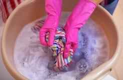 Le mani del ` s delle donne lavano i vestiti nel bacino immagini stock