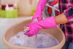 Le mani del ` s delle donne lavano i vestiti nel bacino fotografia stock
