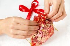 Le mani del ` s delle donne legano una piccola borsa con i regali, accanto ad un contenitore di regalo sulla tavola Fotografia Stock
