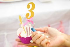 Le mani del ` s delle donne mettono tre candele su fuoco sul bigné di compleanno in tazza rosa e numerano 3 sulla cima Fotografia Stock