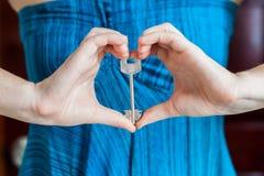 Le mani del ` s delle donne tengono la chiave della casa sotto forma di cuore sui precedenti di una porta di legno Possesso del c immagine stock