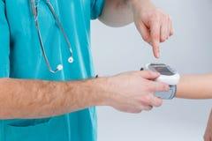 Le mani del ` s di medico premono i bottoni sul tonometer per misurare la pressione del ` s della ragazza isolamento Fine in su fotografie stock