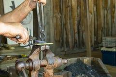 Le mani del ` s del fabbro sul lavoro alla forgia che lavora con l'oggetto hanno tenuto in vice con le tenaglie al Muskogee Oklah fotografia stock