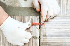 Le mani del ` s del piastrellista stanno allineando le mattonelle Fotografia Stock Libera da Diritti