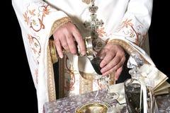 Le mani del sacerdote con vino Fotografie Stock