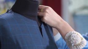 Le mani del sarto che appuntano la scollatura del vestito sul manichino stock footage