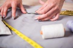 Le mani del sarto che lavorano al nuovo abbigliamento Fotografie Stock