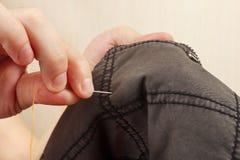 Le mani del sarto cucono i vestiti neri del cotone con la fine dell'ago su fotografie stock libere da diritti