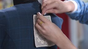 Le mani del sarto da donna che appuntano la decorazione del pizzo per vestirsi video d archivio