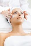 Le mani del terapista applicano la crema al fronte della donna Fotografia Stock