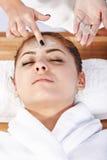 Le mani del terapista applicano la crema al fronte della donna Concetto di cura Immagine Stock Libera da Diritti