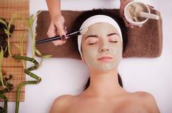 Le mani del terapista applicano la crema al fronte della donna Concetto di cura e della gioventù Immagini Stock Libere da Diritti