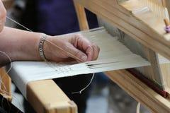 Le mani del tessitore del telaio a mano Immagine Stock