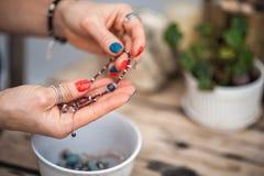 Le mani del tocco della ragazza i gioielli fatti a mano Ragazza e gioielli La donna fatta a mano che decora le pietre si chiude s fotografia stock