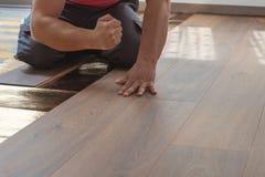 Le mani del tuttofare battono la plancia laminata a porre il pavimento laminato fotografia stock
