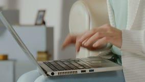 Le mani dell'articolo di battitura a macchina di giovane blogger femminile sul computer portatile, freelance lavoro video d archivio