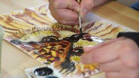 Le mani dell'artista dipingono con una spazzola stock footage