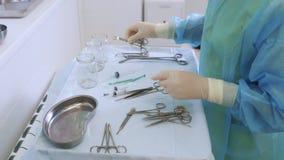 Le mani dell'infermiere del primo piano in guanti sterili prepara gli strumenti medici per la chirurgia di scleroterapia stock footage